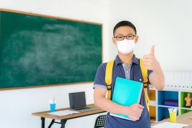 Estudantes asiáticos primários menino polegar para cima e vestindo máscaras sua escola