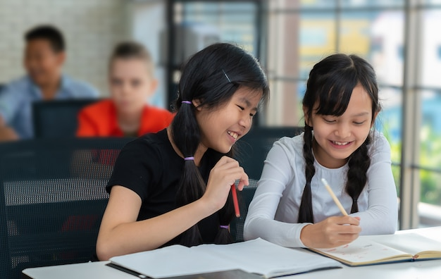 Estudantes asiáticos se divertem escrevendo no caderno em sala de aula
