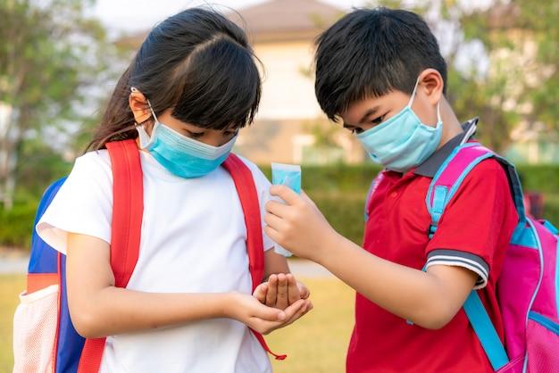 Estudantes asiáticos usam máscara higiênica e pressionam o gel de álcool da garrafa para a irmã da mão para proteger o covid-19 e o vírus epidêmico depois de voltar da escola.