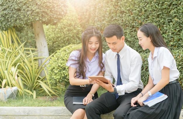 Estudantes asiáticos usando tablet para fazer lição de casa