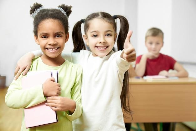 Estudantes bonitas que estão na sala de aula, colegas que mostram os polegares acima. alegre,