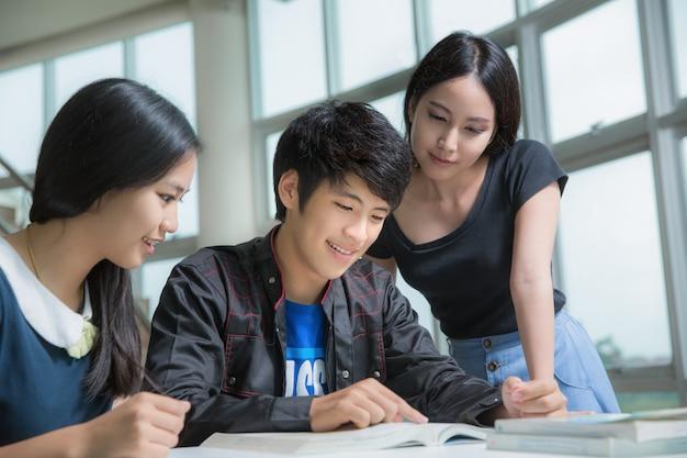 Estudantes da ásia se encontrando na biblioteca da universidade