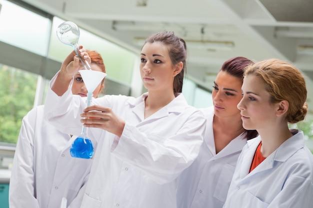 Estudantes de ciência bonito derramando líquido em um balão