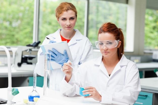 Estudantes de ciências lindos fazendo um experimento
