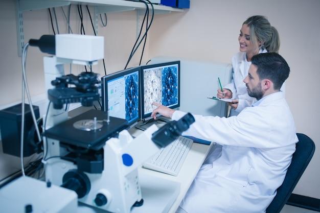 Estudantes de ciências olhando para imagens microscópicas