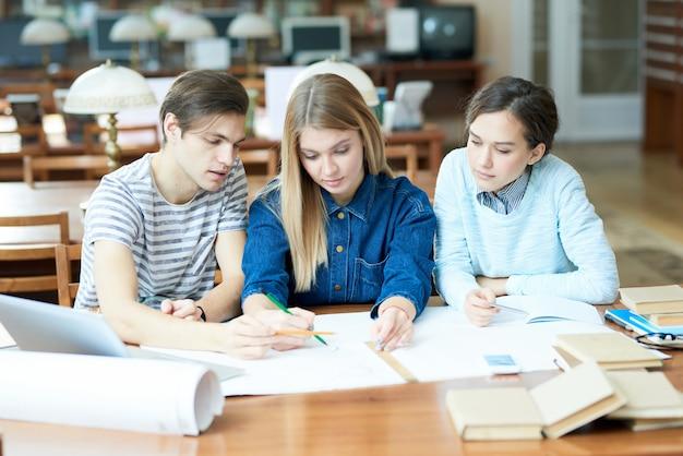 Estudantes de engenharia ocupados discutindo sobre o projeto