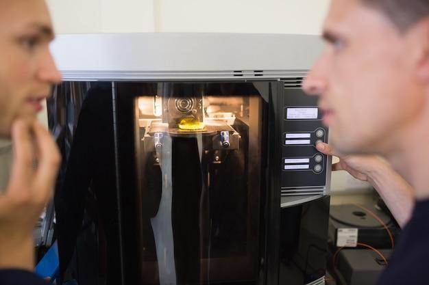 Estudantes de engenharia usando a impressora 3d