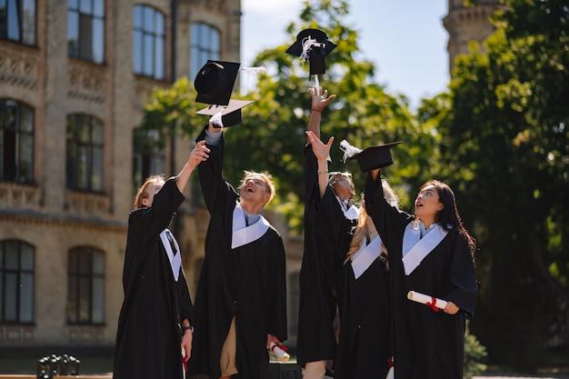 Estudantes de graduação jogando seus bonés de mestrado no pátio da universidade