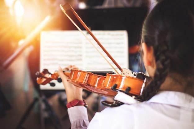 Estudantes de menina tocando violino no grupo.