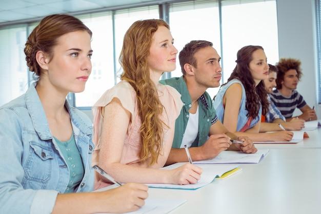 Estudantes de moda tomando notas em sala de aula