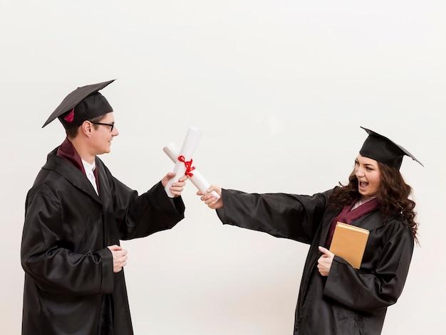 Estudantes de pós-graduação brigando com diplomas