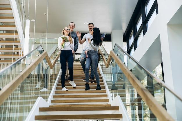 Estudantes descer as escadas com livros na biblioteca