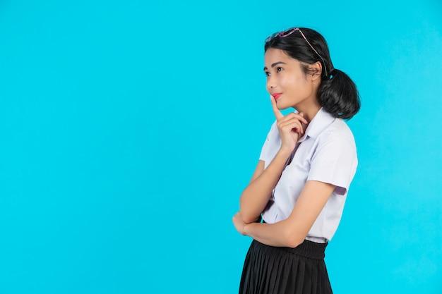 Estudantes do sexo feminino asiáticos posando em várias posições em um azul.