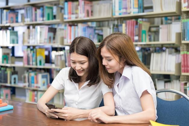 Estudantes do sexo feminino asiáticos sentado à mesa e ler a mensagem de texto