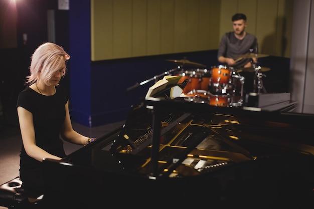Estudantes do sexo feminino e masculino tocando piano e bateria