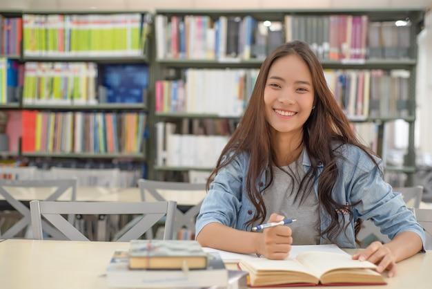 Estudantes do sexo feminino estão à procura de trabalhos de pesquisa.