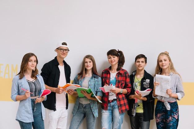 Estudantes em pé com cadernos