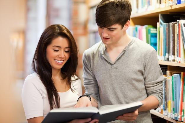 Estudantes felizes a olhar para um livro