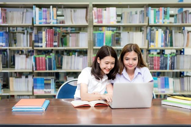 Estudantes felizes asiáticos com o laptop que trabalha e que estuda na biblioteca.