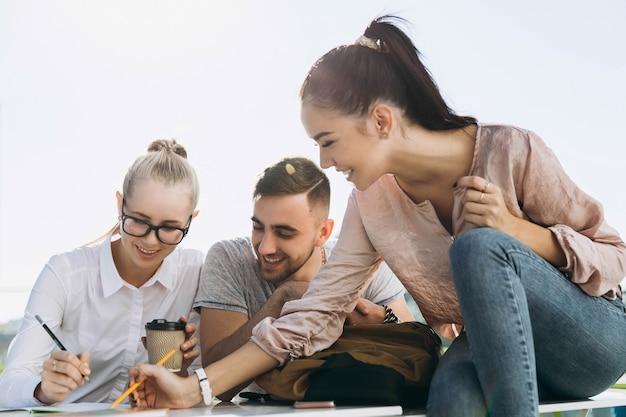 Estudantes felizes trabalham e estudam à mesa no ar fresco