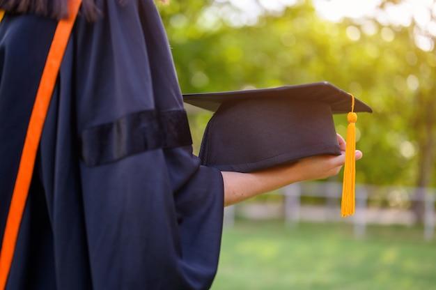 Estudantes fêmeas de cabelos compridos que vestem o plissado preto vestem a expressão da alegria na graduação na universidade.