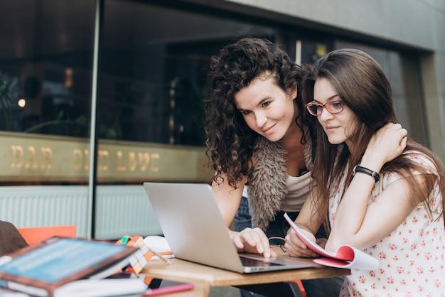 Estudantes inteligentes. duas meninas estão trabalhando com o laptop