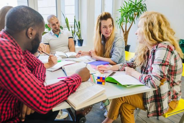 Estudantes inteligentes que trabalham na sala de aula