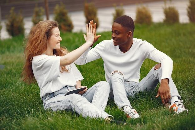 Estudantes inter-raciais se divertem e riem alegremente no parque