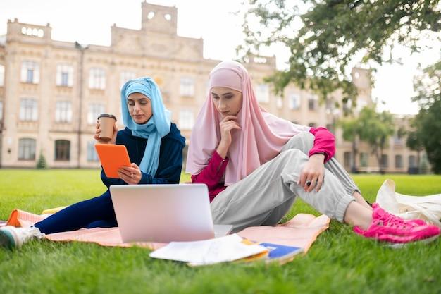 Estudantes internacionais. estudantes internacionais muçulmanos usando laptop enquanto preparam a apresentação