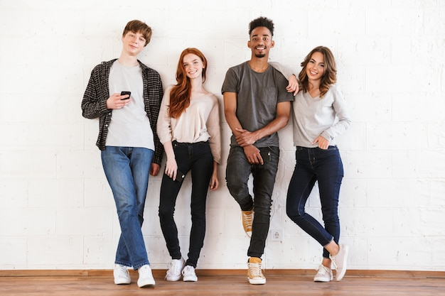 Estudantes jovens amigos sorridentes sobre uma parede branca