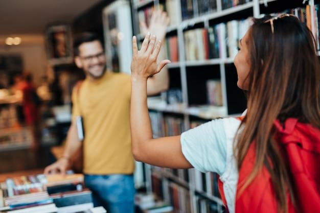 Estudantes jovens atraentes homem e mulher escolhendo livros na livraria.