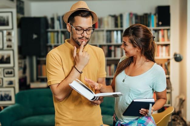Estudantes jovens atraentes homem e mulher sentada na biblioteca da universidade e aprendendo.