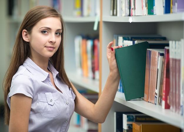 Estudantes jovens felizes que estudam na biblioteca da faculdade pegando um livro da prateleira