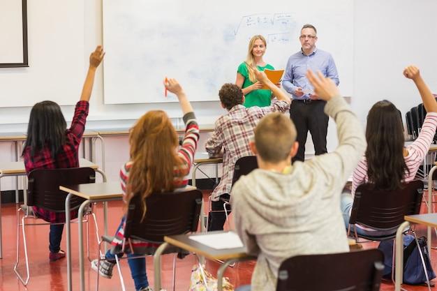 Estudantes levantando as mãos na sala de aula