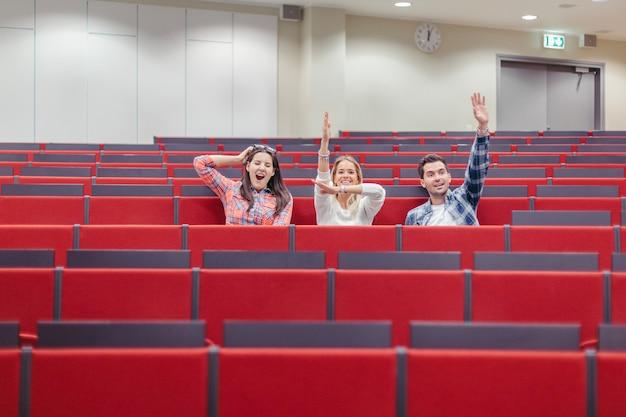 Estudantes levantando as mãos no anfiteatro da universidade