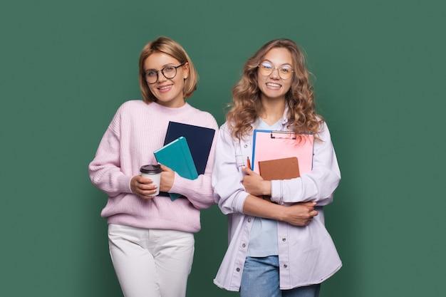Estudantes loiras encantadoras sorrindo em uma parede verde enquanto abraçam alguns livros e bebem um café
