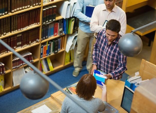 Estudantes maduros no balcão da biblioteca da faculdade