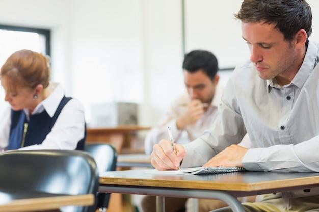 Estudantes maduros que tomam notas na sala de aula