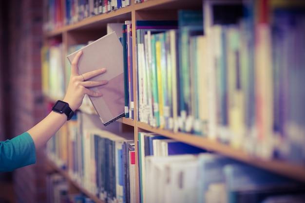 Estudantes mão com smartwatch picking book from bookshelf