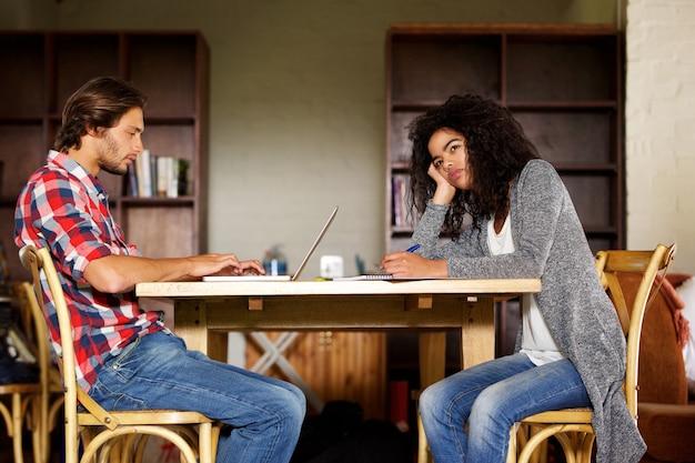 Estudantes masculinos e femininos, sentado em casa estudando