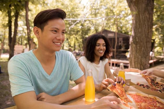 Estudantes multi-étnicos novos de sorriso dos amigos que bebem fora o suco que come a pizza.