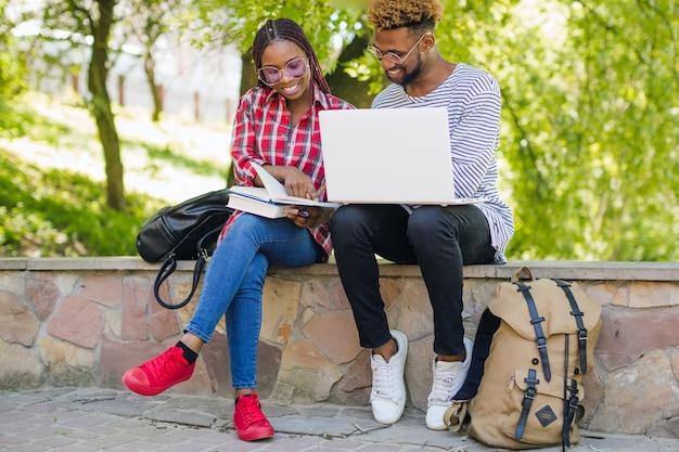 Estudantes negros alegres estudando juntos
