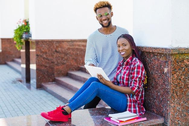 Estudantes negros de conteúdo em pé com touchpad