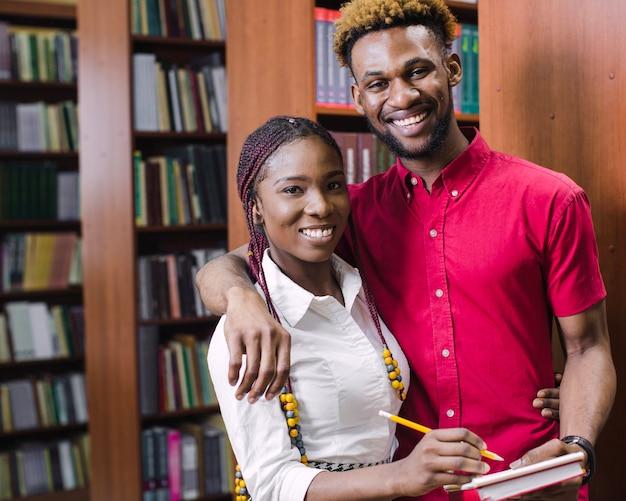 Estudantes negros posando com bloco de notas