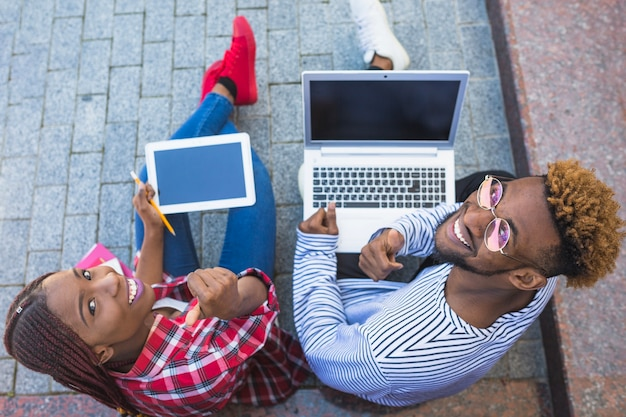Estudantes negros posando com gadgets