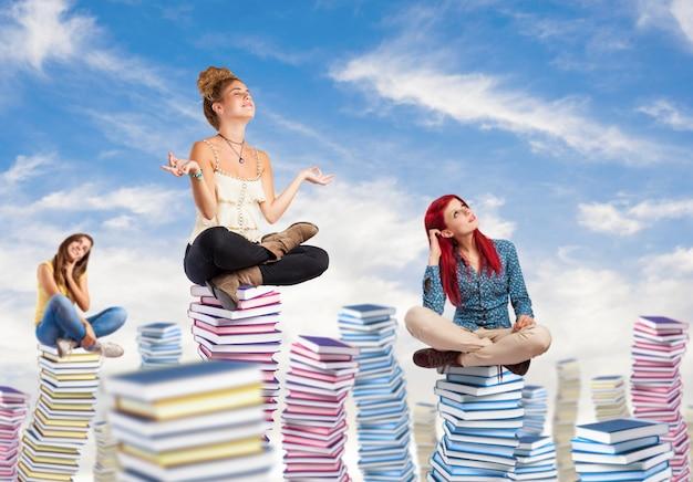Estudantes pensativo que senta em colunas de livros