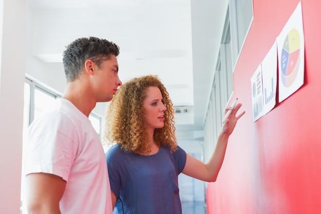 Estudantes que estudam junto com gráficos na parede