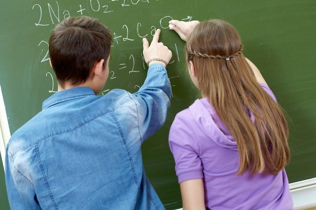 Estudantes que fazem problemas de matemática no quadro-negro