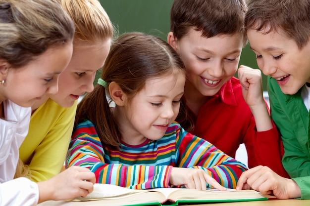 Estudantes que têm um bom tempo durante a leitura em sala de aula