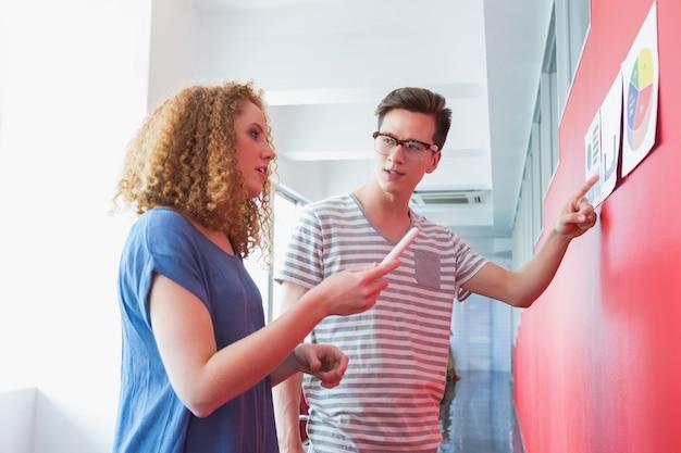 Estudantes que trabalham em conjunto com gráficos
